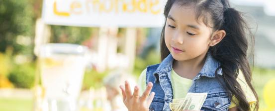 Little girl counting proceeds from sales